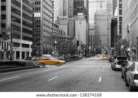 Manhattan, New York city in early morning with almost no traffic on the street between many skycrapers with yellow caps motion blurred in black and white composition - stock photo