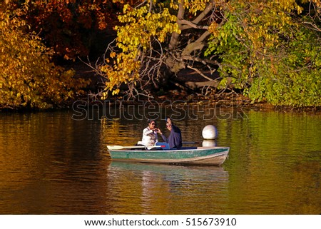 MANHATTAN, NEW YORK CITY/USA - NOVEMBER 13, 2016: A couple in a rowboat, taking a selfie while making a heart with their hands, in the Lake of New York City's Central Park.