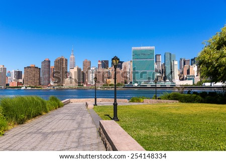 Manhattan New York sunny skyline from green park turf East River NYC USA - stock photo