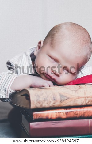 MANHATTAN, NEW YORK USA – OCTOBER 11 2014: A newborn baby is sleeping on a pile of books.
