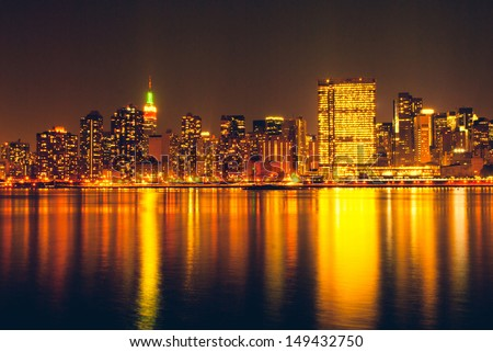 Manhattan skyline by night, reflection on Hudson river. Urban travel concept