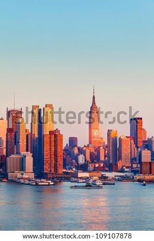 Manhattan Skyline illuminated by sunset - stock photo