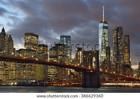 Manhattan skyline with Brooklyn Bridge at night. - stock photo