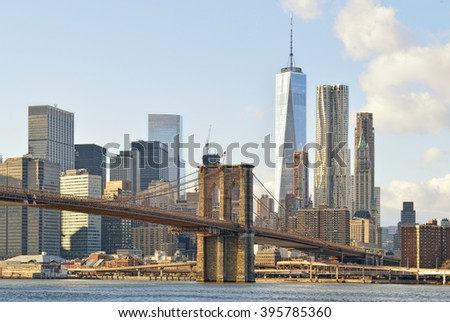 Manhattan skyline with Brooklyn Bridge at sunny day. - stock photo