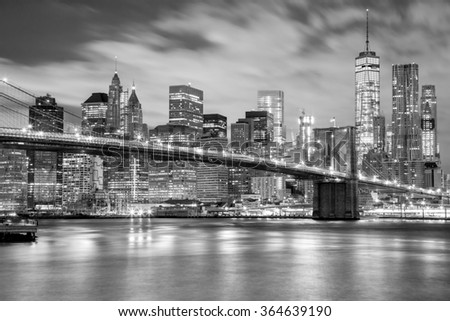 Manhattan skyscrapers and Brooklyn Bridge - city illuminations, black and white colors, New York, USA - stock photo