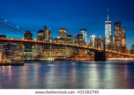 Manhattan with skyscrapers and Brooklyn Bridge by evening, New York City illumination - stock photo