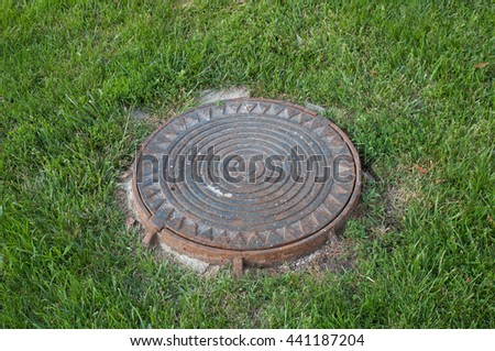 manhole cover on the grass - stock photo