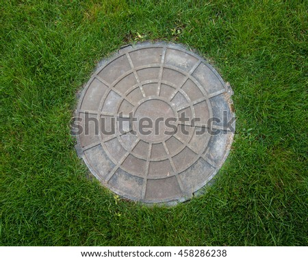 Manhole in grass - stock photo