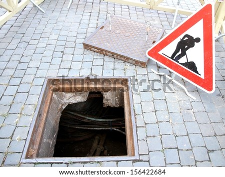 manhole opened for excavation and repair the cable and the signal of caution work in progress - stock photo
