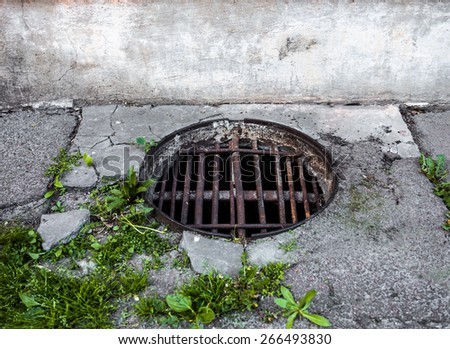 Manhole with the handmade metal armature cover in the cracked concrete and asphalt surface - stock photo