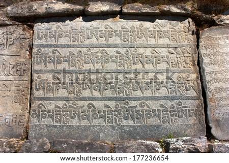 Mani wall and stone with buddhist symbols  - stock photo