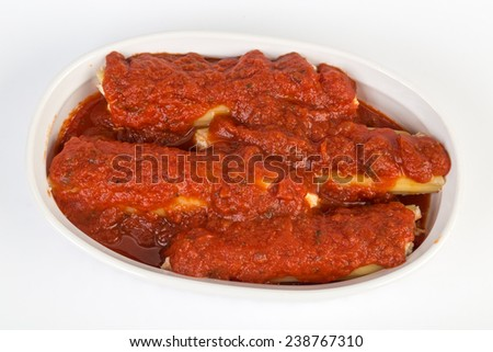 Manicotti pasta in small baking dish being prepared with tomato sauce and cheese.  Ready for the oven. - stock photo