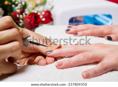 manicure and Hands with uv lamp for nails - stock photo