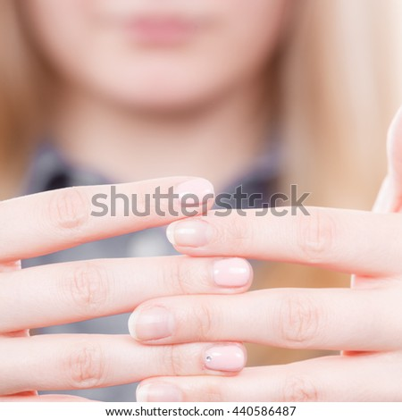 Manicure and hygiene concept. Blonde casual woman presents hands fingers. Girl with one hand coloured by hybrid nail polish and other without.