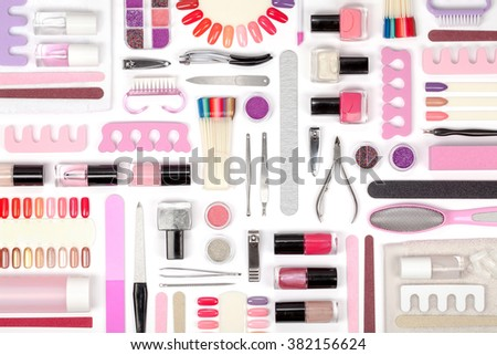 manicure and pedicure tools and other essentials on white background top view. flat lay composition in pink colors - stock photo