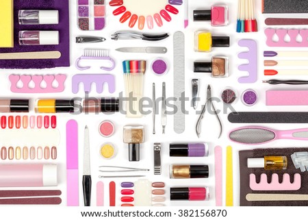 manicure and pedicure tools and other essentials on white background top view. flat lay composition in pink, violet and yellow colors - stock photo
