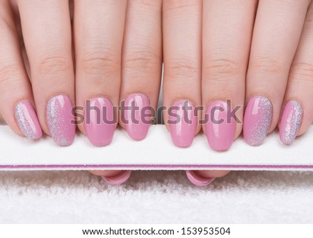 Manicure -  Beautifully manicured woman's fingernails with nice pink nail polish holding nail file. Selective focus. - stock photo