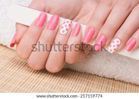 Manicure - Beauty treatment photo of nice manicured woman fingernails holding nail file. Feminine nail art with nice glitter, pink and white nail polish. - stock photo
