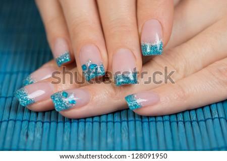 Manicure - Beauty treatment photo of nice manicured woman fingernails. Very interesting nail art with glitter blue and silver nail polish. - stock photo