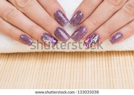 Manicure - Beauty treatment photo of nice manicured woman fingernails. Very interesting nail art with glitter purple, pink and silver nail polish - stock photo