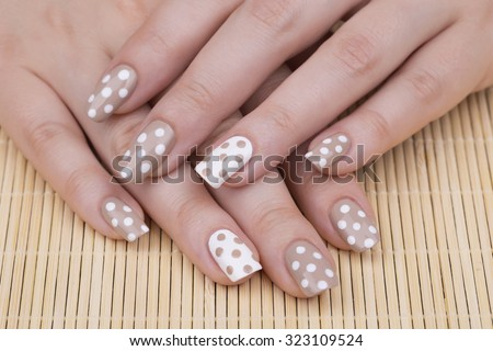 Manicure - Beauty treatment photo of nice manicured woman fingernails. Very nice feminine nail art with nice nude and white nail polish. Selective focus. - stock photo