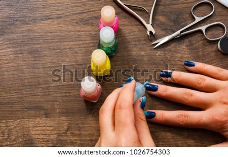 Manicure. Closeup of a woman hand painting her nails with nail polish on a wooden background.