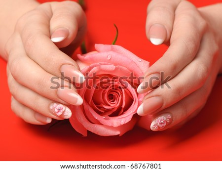 Manicure. Female hands on red background. Well-groomed female hands with a decorative element - a flower