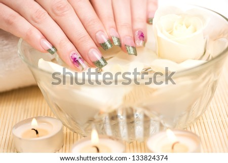 Manicure - Hands dipping into a beauty treatment bowl with rose petals and preparing for getting spa procedure.