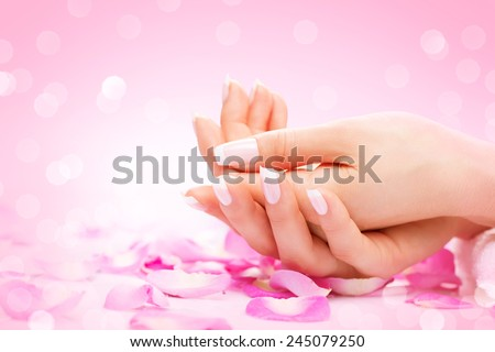 Manicure, Hands spa Beautiful woman hands, soft skin, beautiful nails with pink rose flowers petals. Healthy Woman hands. Beauty salon. Beauty treatment.  Female nails with beautiful french manicure  - stock photo