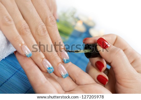 Manicure - manicure treatment, applying cuticle oil on woman nails with very interesting nail art. - stock photo