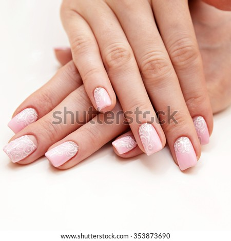 Manicure on long nails covered with pink roses  - stock photo