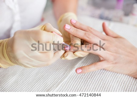 Manicure process in a beauty salon. Close up photo