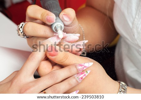 Manicure process in beauty salon showing making of artificial nails. - stock photo