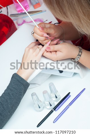 Manicure process in beauty salon showing making of beautiful drawings on artificial nails. - stock photo