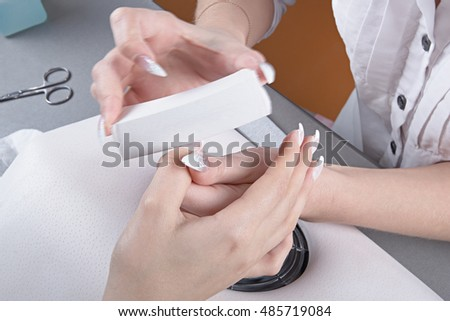 Manicure. Processing of extended nails by a whetstone