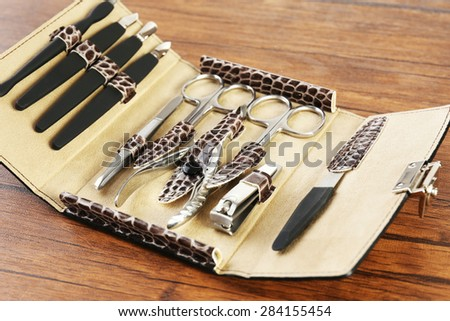 Manicure set in open case on wooden table, closeup - stock photo
