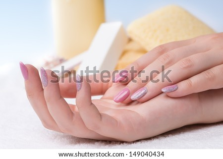 Manicure - very nice pink nail polish with glitter silver details on fingernails. Selective focus.  - stock photo