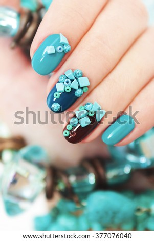 Manicure with blue and brown lacquer decorated with beads and turquoise. - stock photo