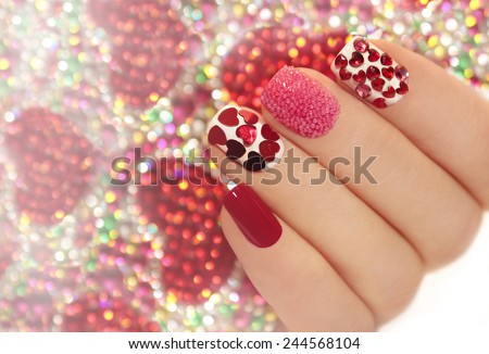 Manicure with rhinestones in the shape of hearts and pink balls on white and red nail Polish on a brilliant background. - stock photo