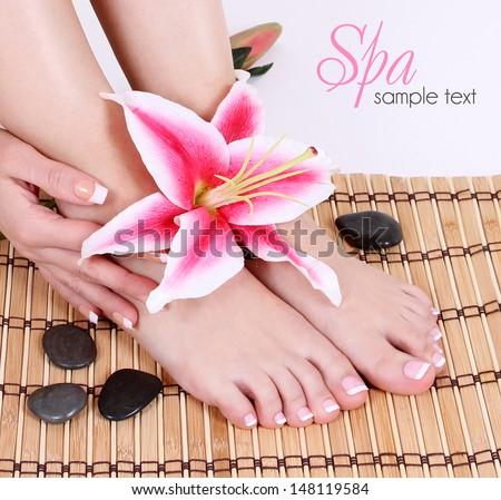 Manicured female bare feet with pink lily flower and spa stones over bamboo mat. Feet care.  - stock photo
