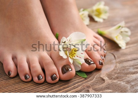 Manicured female feet with flowers on wooden background