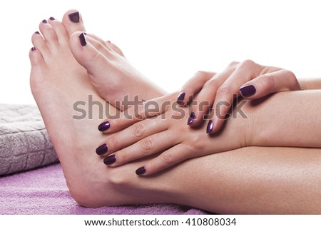 Manicured hands stroke bare feet painted with dark nail polish by gray towel on plush purple spa table