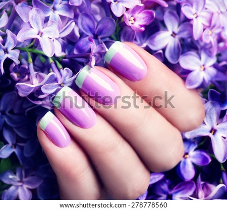 Manicured nails Nail Polish art design. Violet with green colors Art Manicure. Nail Polish. Beauty hands. Fashion Stylish Trendy Colorful Nails  - stock photo