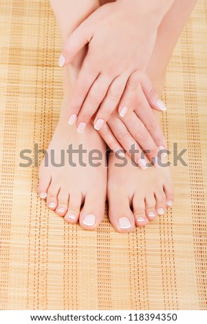 Manicured women's hands crossed on his feet - stock photo