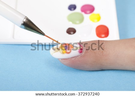 Manicures in the salon. Master makes nail design - stock photo