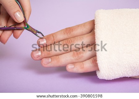 Manicurist doing manicure for man in beauty salon - stock photo