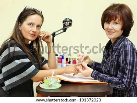 Manicurist makes manicure by nailfile for woman in beauty salon; two woman look at camera - stock photo