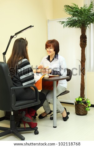 Manicurist makes manicure for woman in beauty salon and looks at customer; client sits with her back to camera - stock photo