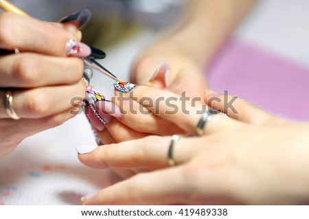 Manicurist master makes manicure on young woman hand      - stock photo
