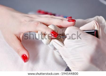 Manicurist nails handles client nail file shot closeup - stock photo